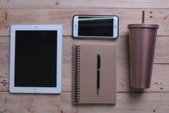 Lieu de travail de bureau Fond en bois de bureau avec l'ordinateur portable, le téléphone portable, la tasse d'écouteur, inoxydab images stock
