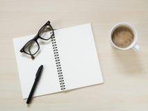 Lieu de travail - carnet avec les lunettes, le stylo et la tasse de café chaud Images stock