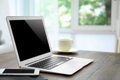 Lieu de travail confortable avec l'ordinateur portable moderne Photo stock