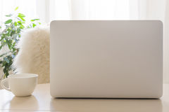 Lieu de travail confortable avec l'ordinateur portable moderne et la tasse blanche Maquette Photographie stock