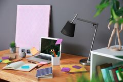 Lieu de travail confortable avec l'ordinateur portable sur la table Photos stock