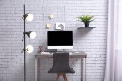 Lieu de travail confortable avec l'ordinateur sur le bureau Photo stock