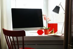 Lieu de travail confortable moderne avec l'ordinateur sur le filon-couche de fenêtre Photos stock