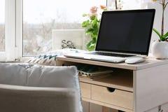 Lieu de travail créatif avec l'ordinateur portable près du windowsil Images libres de droits