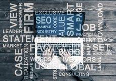 Lieu de travail d'affaires avec l'ordinateur portable et les mots conceptuels d'affaires Images libres de droits