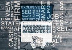Lieu de travail d'affaires avec l'ordinateur portable et les mots conceptuels d'affaires Image libre de droits