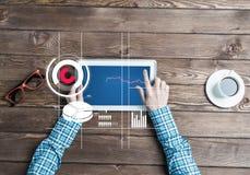 Lieu de travail d'affaires avec la tasse de café de dispositif de comprimé et les graphiques et les diagrammes de media Photo stock