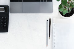 Lieu de travail d'affaires avec un bloc-notes, une calculatrice, un carnet, une plante verte Images libres de droits