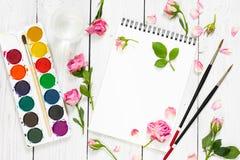 Lieu de travail d'artiste Paper, de brosses, de peintures d'aquarelle et de rose Photographie stock libre de droits