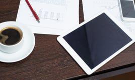 Lieu de travail d'homme d'affaires avec le comprimé numérique, le smartphone, la tasse de café et les diagrammes Le concept d'une Photographie stock