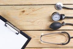 Lieu de travail d'un docteur Presse-papiers et stéthoscope médicaux sur le fond en bois de bureau Vue supérieure Images stock