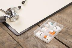 Lieu de travail d'un docteur Stéthoscope, presse-papiers, pilules et toute autre substance sur le bureau en bois Photos stock