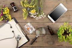 Lieu de travail d'un docteur Stéthoscope, presse-papiers, pilules, smartphone et toute autre substance sur le bureau en bois Photos libres de droits