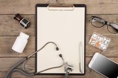 Lieu de travail d'un docteur Stéthoscope, presse-papiers, pilules, smartphone et toute autre substance sur le bureau en bois Photo stock