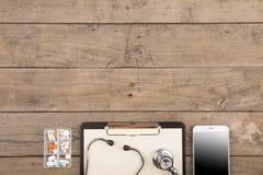 Lieu de travail d'un docteur Stéthoscope, presse-papiers, pilules, smartphone et toute autre substance sur le bureau en bois Image stock