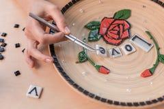 Lieu de travail d'un maître de mosaïque : mains femelles présentant un élément de mosaïque sur la table Photographie stock