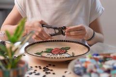 Lieu de travail d'un maître de mosaïque : mains femelles présentant un élément de mosaïque sur la table Images libres de droits