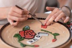 Lieu de travail d'un maître de mosaïque : mains femelles présentant un élément de mosaïque sur la table Image libre de droits