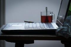 Lieu de travail d'un programmeur ou d'un auteur L'ordinateur portable est sur la table avec le thé, la bière et une cigarette Photographie stock libre de droits