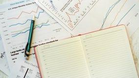 Lieu de travail dans le bureau, le bloc-notes et les graphiques Photos stock