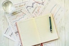 Lieu de travail dans le bureau, le bloc-notes et les graphiques Photographie stock