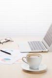 Lieu de travail de bureau avec du café, l'ordinateur portable et les approvisionnements Photo stock