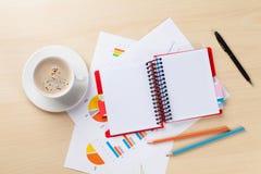 Lieu de travail de bureau avec du café, le bloc-notes et les diagrammes Photo libre de droits