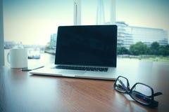 Lieu de travail de bureau avec l'ordinateur portable d'écran vide Image stock