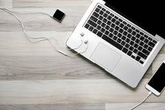 Lieu de travail de bureau avec l'ordinateur portable et le smartphone sur la table en bois Image stock