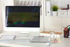 Lieu de travail de bureau avec l'ordinateur portable et le téléphone intelligent sur la table en bois Photographie stock libre de droits