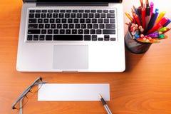 Lieu de travail de bureau avec l'ordinateur portable et le téléphone intelligent sur les tables en bois Images stock