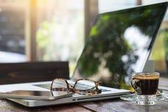Lieu de travail de bureau avec l'ordinateur portable et les verres sur la table en bois Image libre de droits