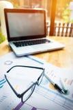 Lieu de travail de bureau avec l'ordinateur portable et les verres sur la table en bois Photos libres de droits