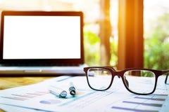 Lieu de travail de bureau avec l'ordinateur portable et les verres sur la table en bois Images libres de droits
