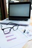Lieu de travail de bureau avec l'ordinateur portable et les verres sur la table en bois Image stock