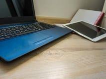 Lieu de travail de bureau avec l'ordinateur portable, le carnet et le comprimé sur la table en bois Image libre de droits