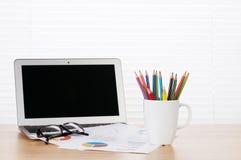 Lieu de travail de bureau avec l'ordinateur portable, les rapports et les crayons Photo stock