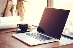 Lieu de travail de bureau avec l'ordinateur portable sur la table en bois contre les fenêtres photos libres de droits