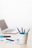 Lieu de travail de bureau avec la tasse, l'ordinateur portable et les approvisionnements de café Photographie stock libre de droits