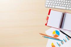 Lieu de travail de bureau avec le PC, les diagrammes et le bloc-notes Images stock