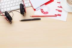 Lieu de travail de bureau avec les diagrammes, le café et les écouteurs Image stock