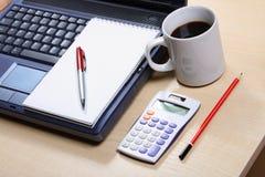 La vie toujours avec une tasse bleue de carnet de coffe, calculatrice, protection, stylo rouge Photographie stock