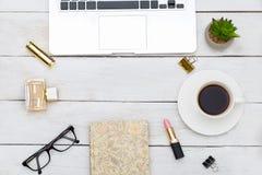 Lieu de travail de bureau de vue supérieure avec l'ordinateur portable, les cosmétiques d'or et la tasse de Image libre de droits