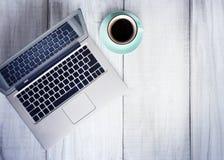 Lieu de travail de tasse de café d'ordinateur portable sur l'espace vide de fond en bois Photo libre de droits