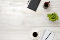 Lieu de travail de vue supérieure avec la tasse du café, de la plante en pot, du carnet, du crayon et du stylo sur la table en bo Photos stock