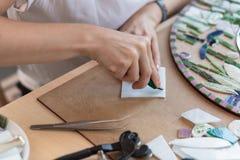 Lieu de travail du maître de mosaïque : le ` s de femmes remet l'outil de fixation pour des détails de mosaïque en cours de faire Image libre de droits
