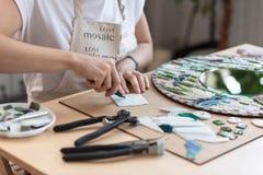 Lieu de travail du maître de mosaïque : le ` s de femmes remet l'outil de fixation pour des détails de mosaïque en cours de faire Photographie stock