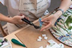 Lieu de travail du maître de mosaïque : le ` s de femmes remet l'outil de fixation pour des détails de mosaïque en cours de faire Photo stock