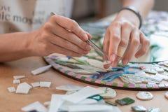 Lieu de travail du maître de mosaïque : le ` s de femmes remet l'outil de fixation pour des détails de mosaïque en cours de faire Image stock