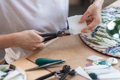Lieu de travail du maître de mosaïque : le ` s de femmes remet l'outil de fixation pour des détails de mosaïque en cours de faire Photos stock